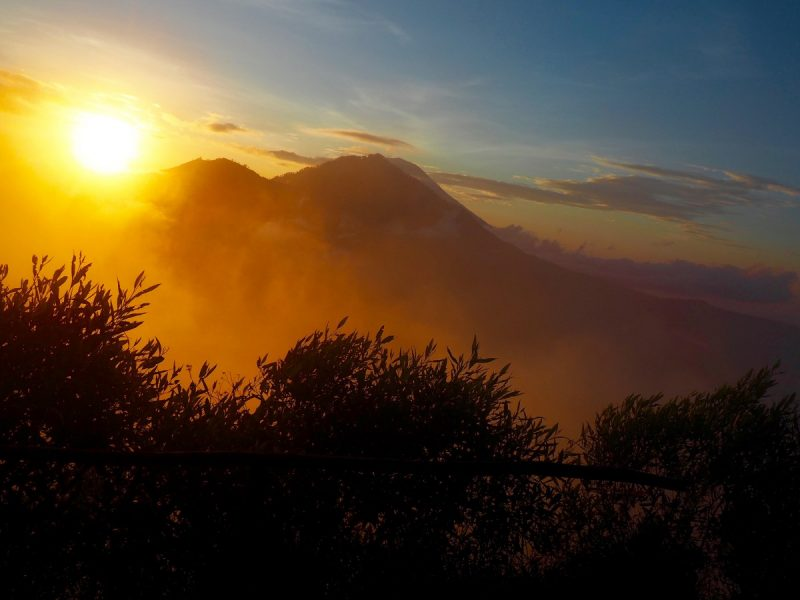 The sun over Mount Batur in Indonesia, a popular place for backpacks to take part in a Sunrise trek