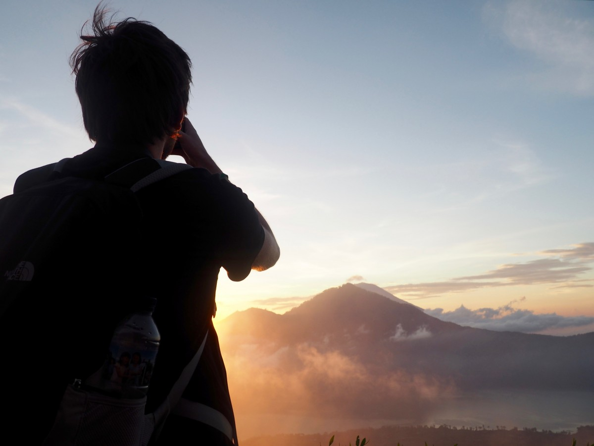 A man standing in front of the sunrise at the top of Mount Batur, Indonesia