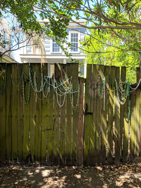 mardi gra beads on fence in new orleans
