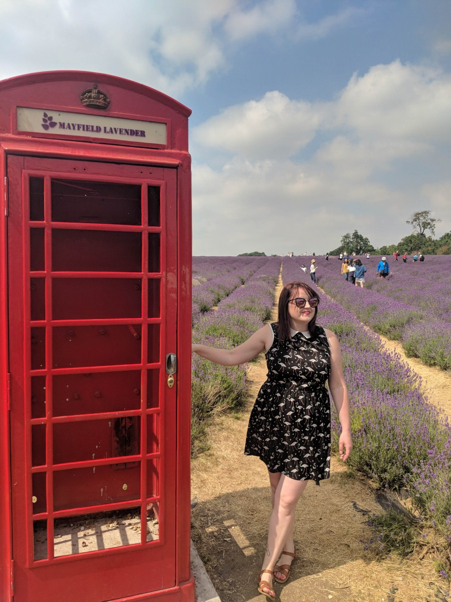a lady standing next to a telephone box photo prop in the mayfield lavender fields, london