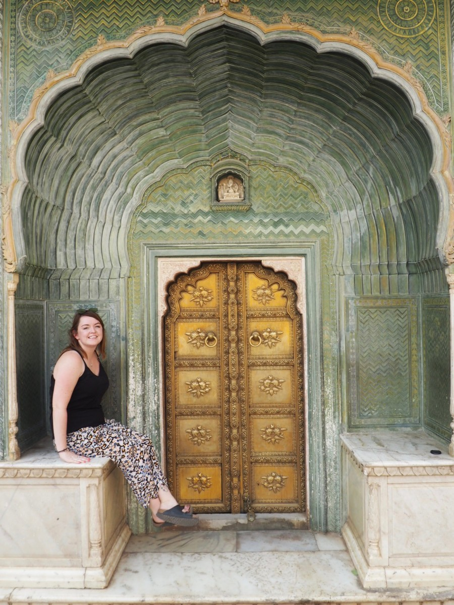 Lady sitting in Jaipur wearing long loose trousers. It is advisable not to bare your legs in most parts of india