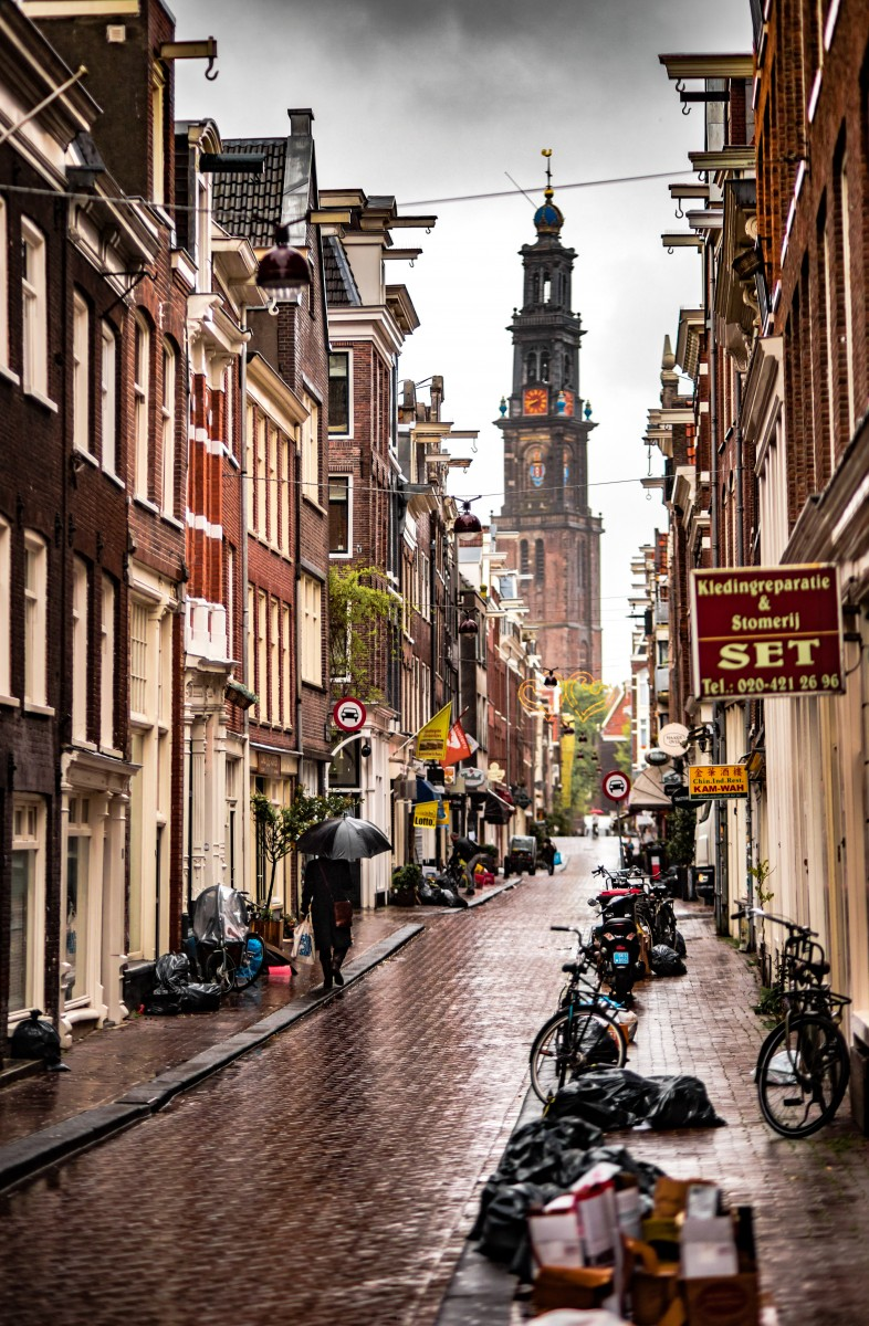Amsterdam city in the rain. I prefer visiting during the summer to save money by spending time outside.