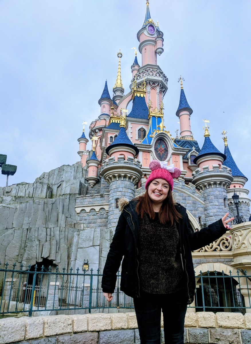 lady in front of they disneyland paris castle, a great place to get a photo with no people in the background