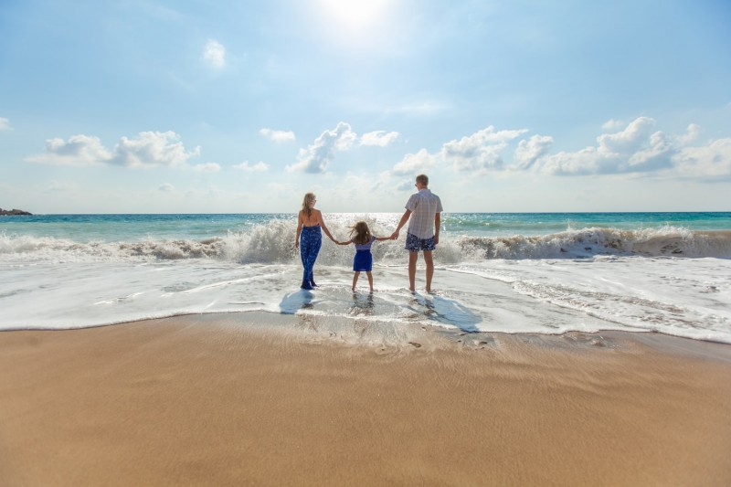 family standing at the beach on holiday won on a travel competition